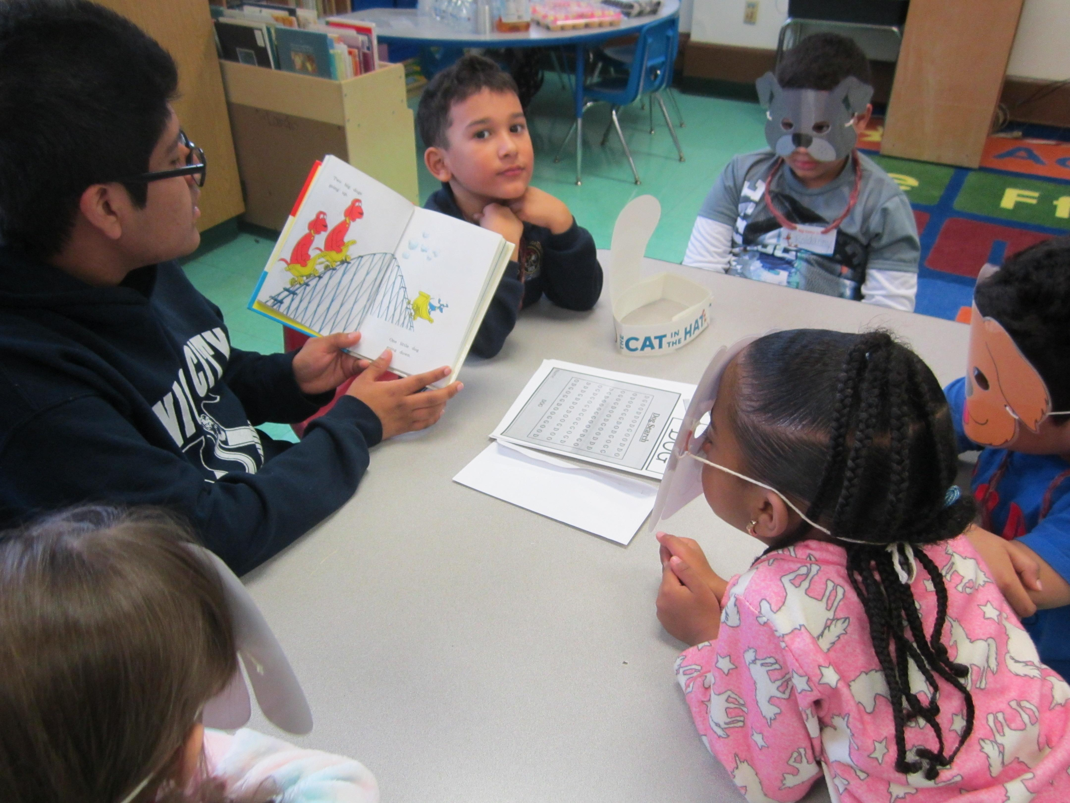 UCHS male student reading to a small group of children