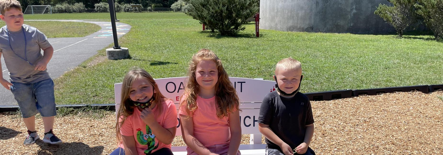 photo of students sitting on the Buddy Bench