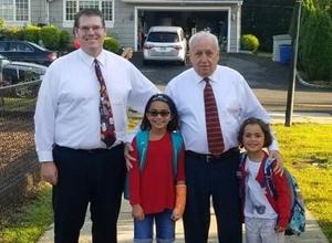 Two Wilson students receive special escort from principal Joseph Malanga and school counselor Frank Uveges on Walk to School Day.