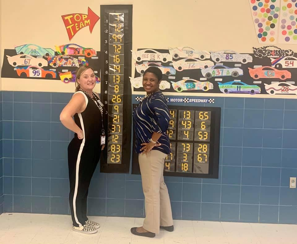 Mrs Rogers and Mrs. Smith in front of fundraiser leader board.