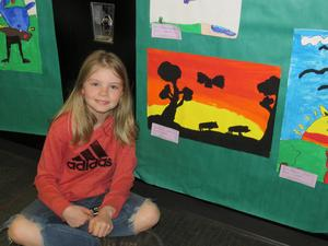 An elementary student sits beside her artwork.
