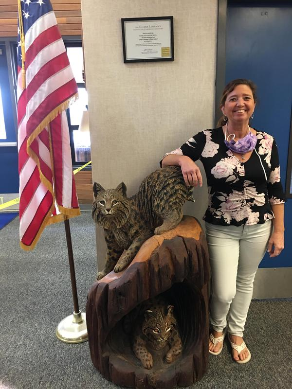 Kimberly Szymanski standing in front of a bobcat statue