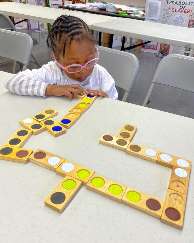 A young student playing a domino game