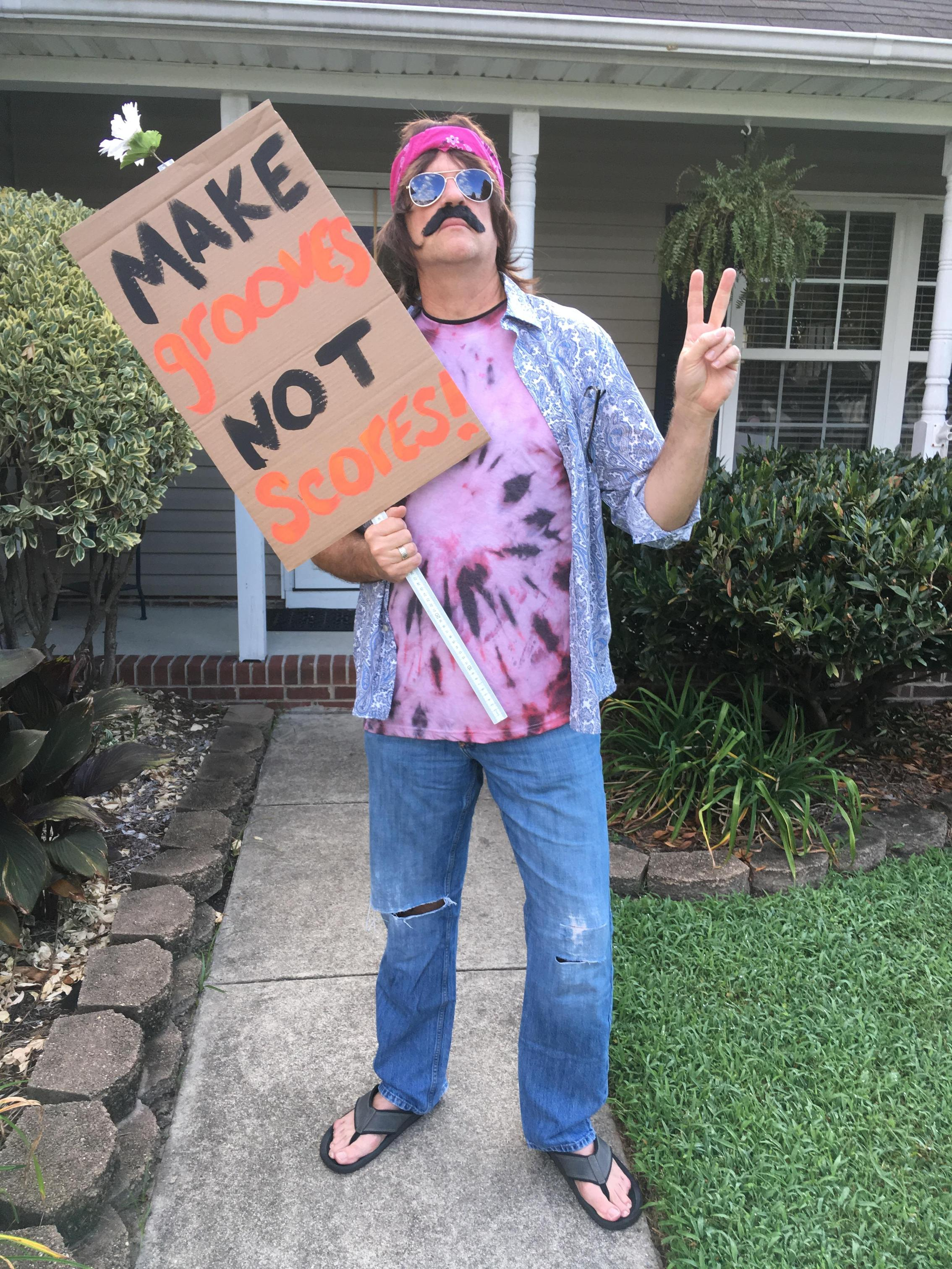 mr. brennan dressed as a hippie for convocation skit