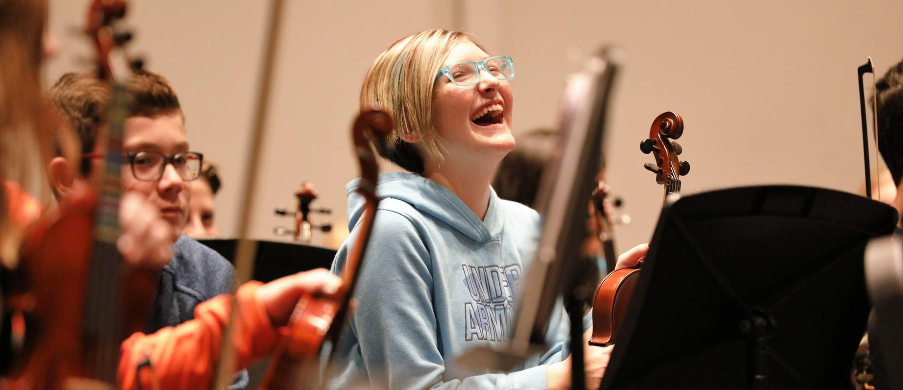 girl laughing in orchestra class