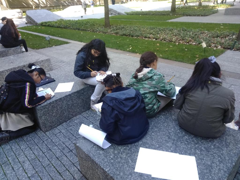 five girls seated and drawing
