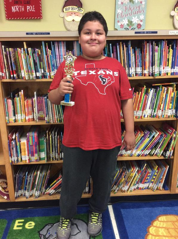 spelling bee champion with trophy.