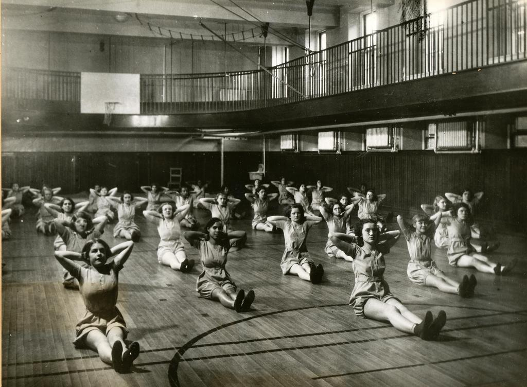 Large group of girls doing situps in the gymnasium