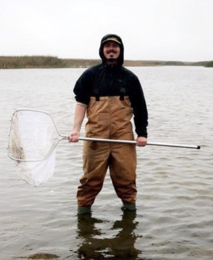 Jaden Kelly; alumni student who works in environmental science in a marsh holding a fishing net