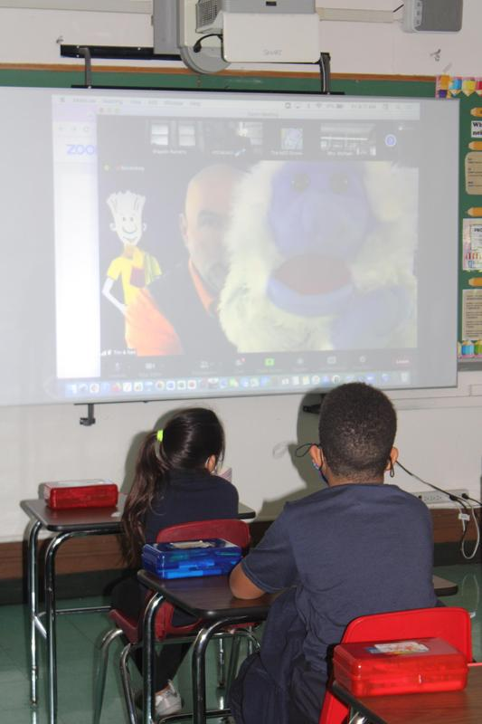 Man with puppet projected on smart board