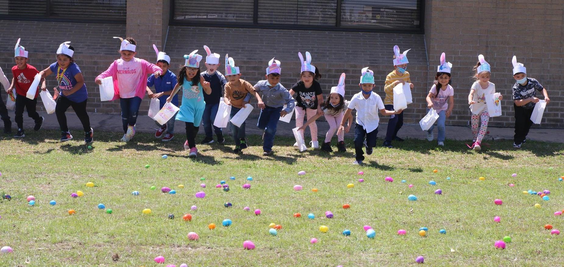 kinder students hunt for numbered easter eggs