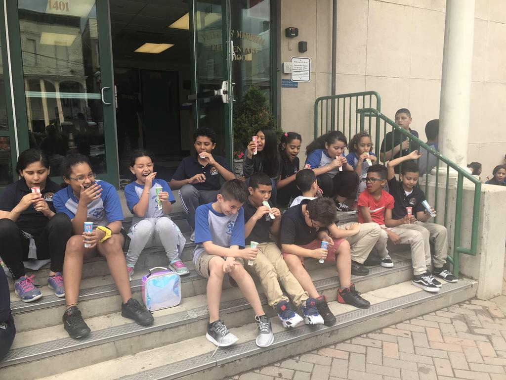 kids enjoying cold treats on the steps of the school