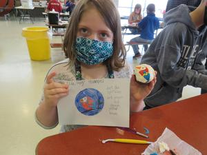 A  3rd grader shows her drawn art design and how it turned out on her cupcake.