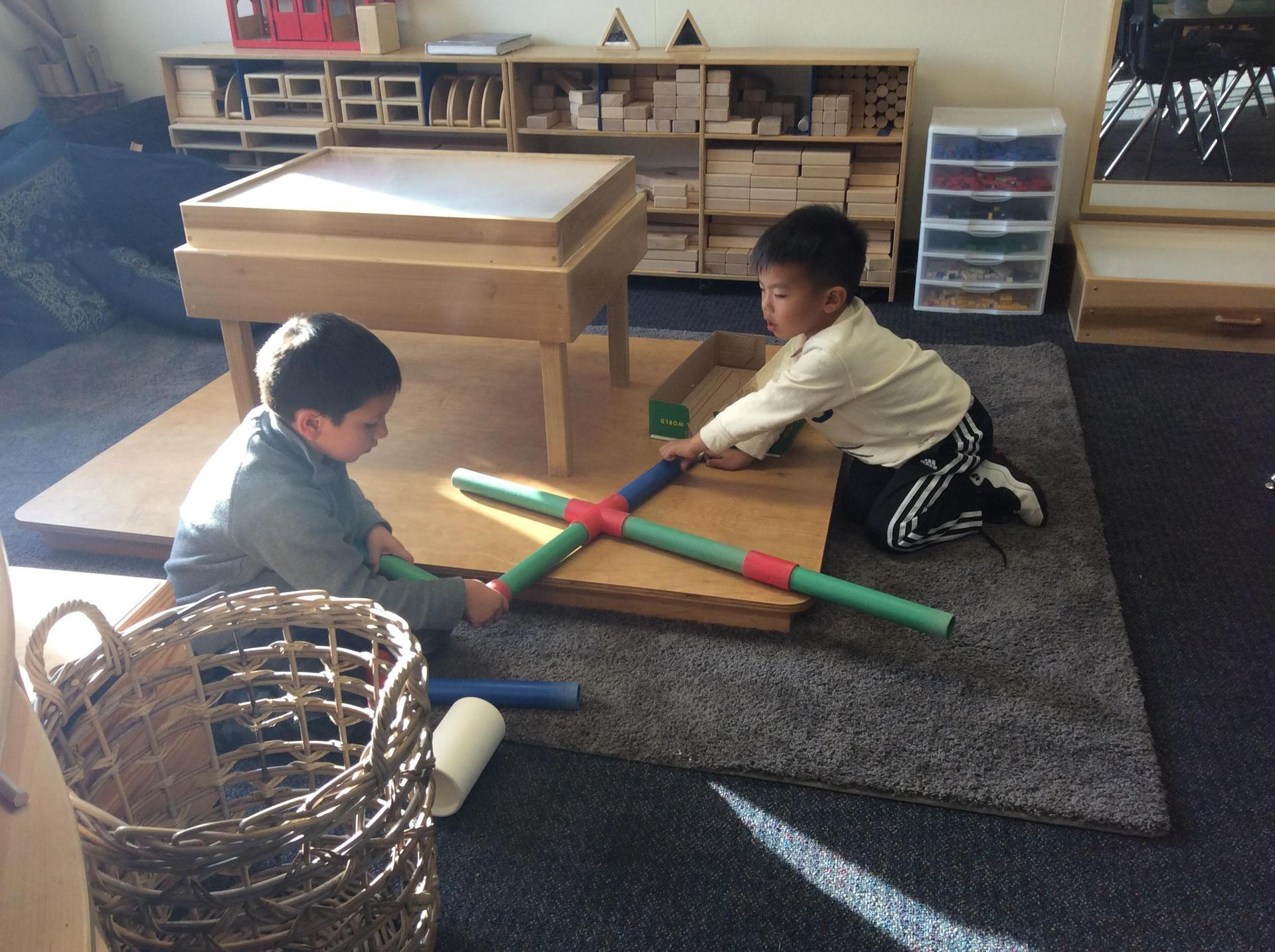 Children playing collaboratively on a platform in the block area of the classroom.