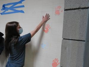 A senior pushes her hand to the wall to leave her print.