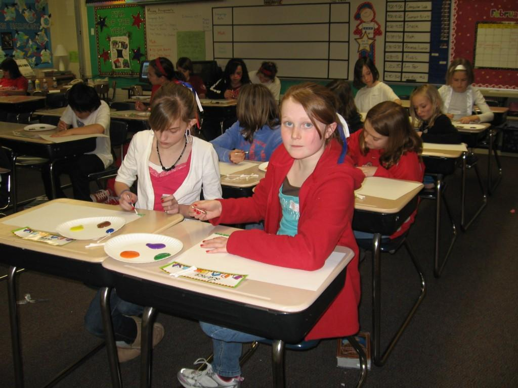 students create art with paints at their desks
