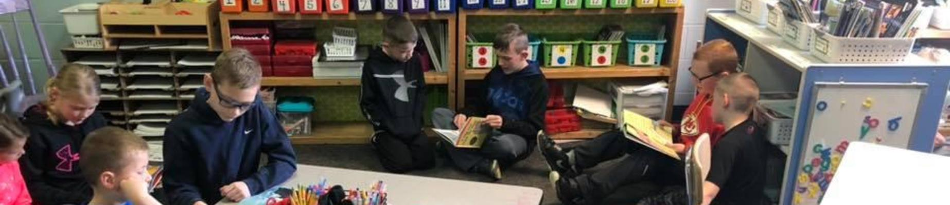 Elementary School students reading to Primary School students