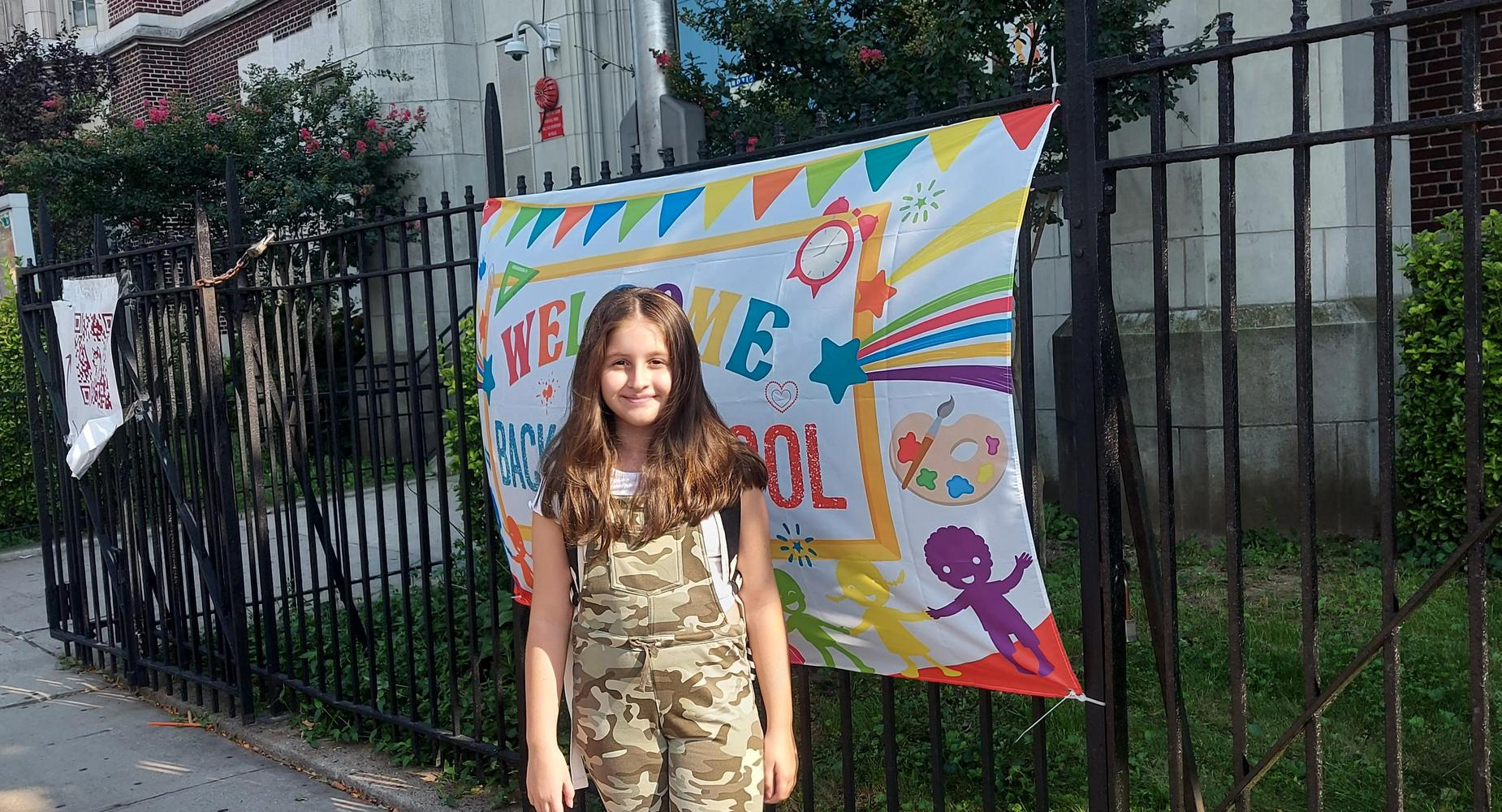 female student in front of welcome back to school banner
