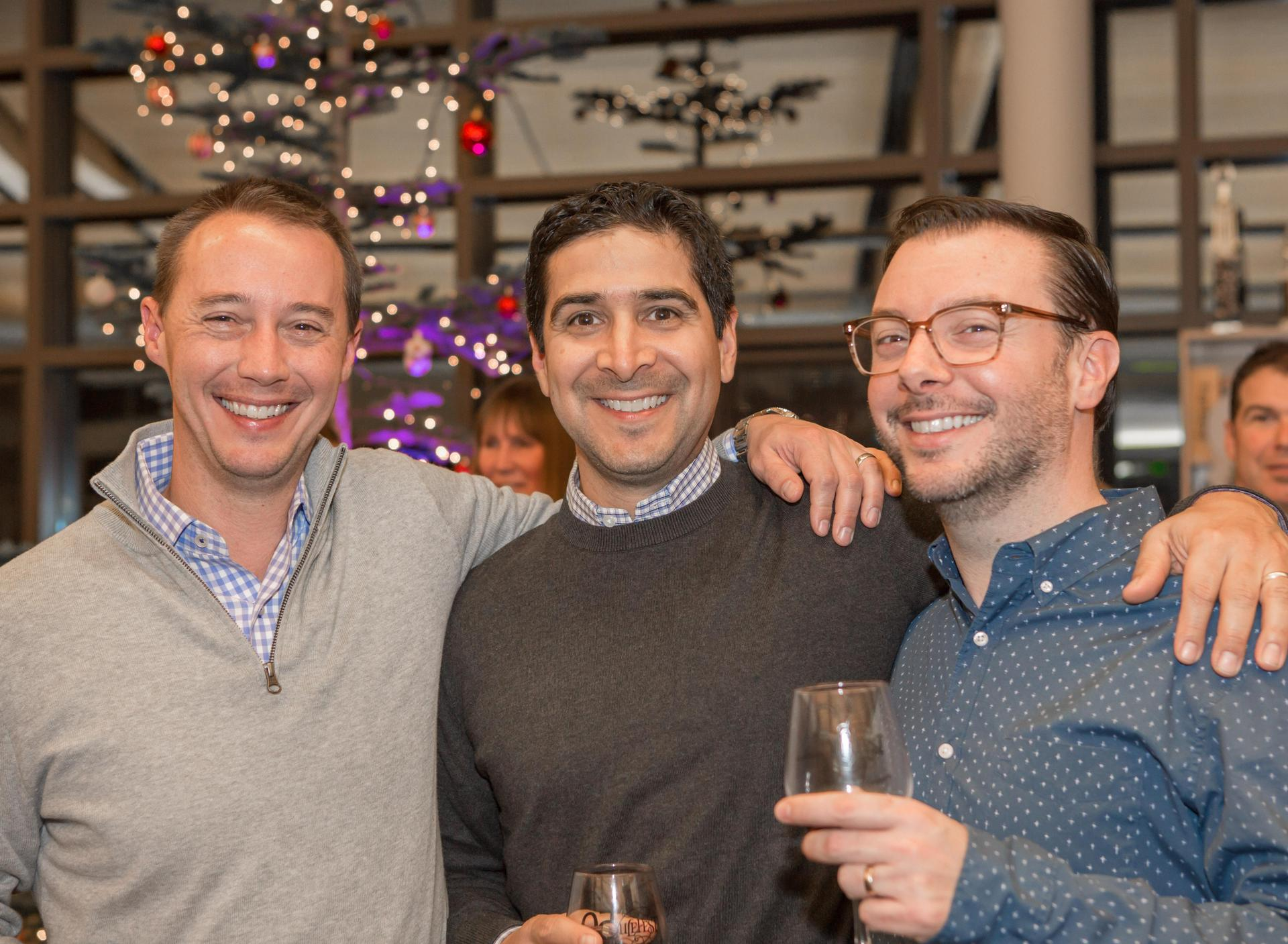 three men pose and smile at event
