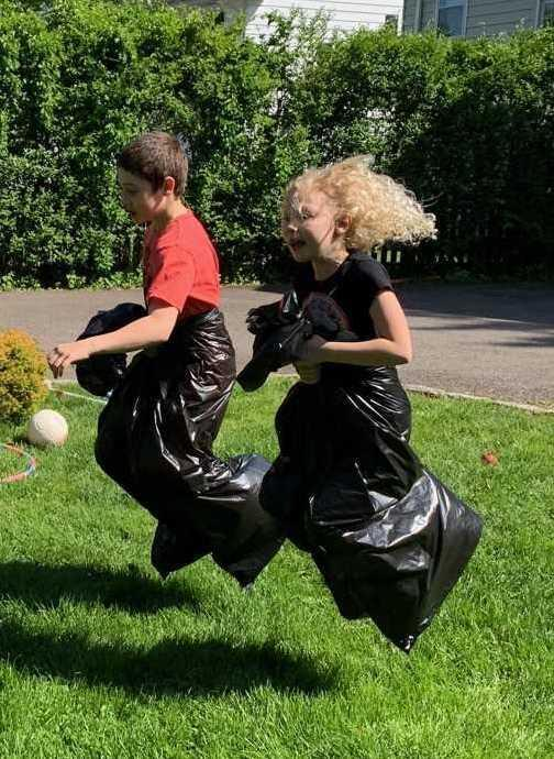 Photo of two Franklin siblings doing a sack race in garbage bags during Franklin virtual field day.