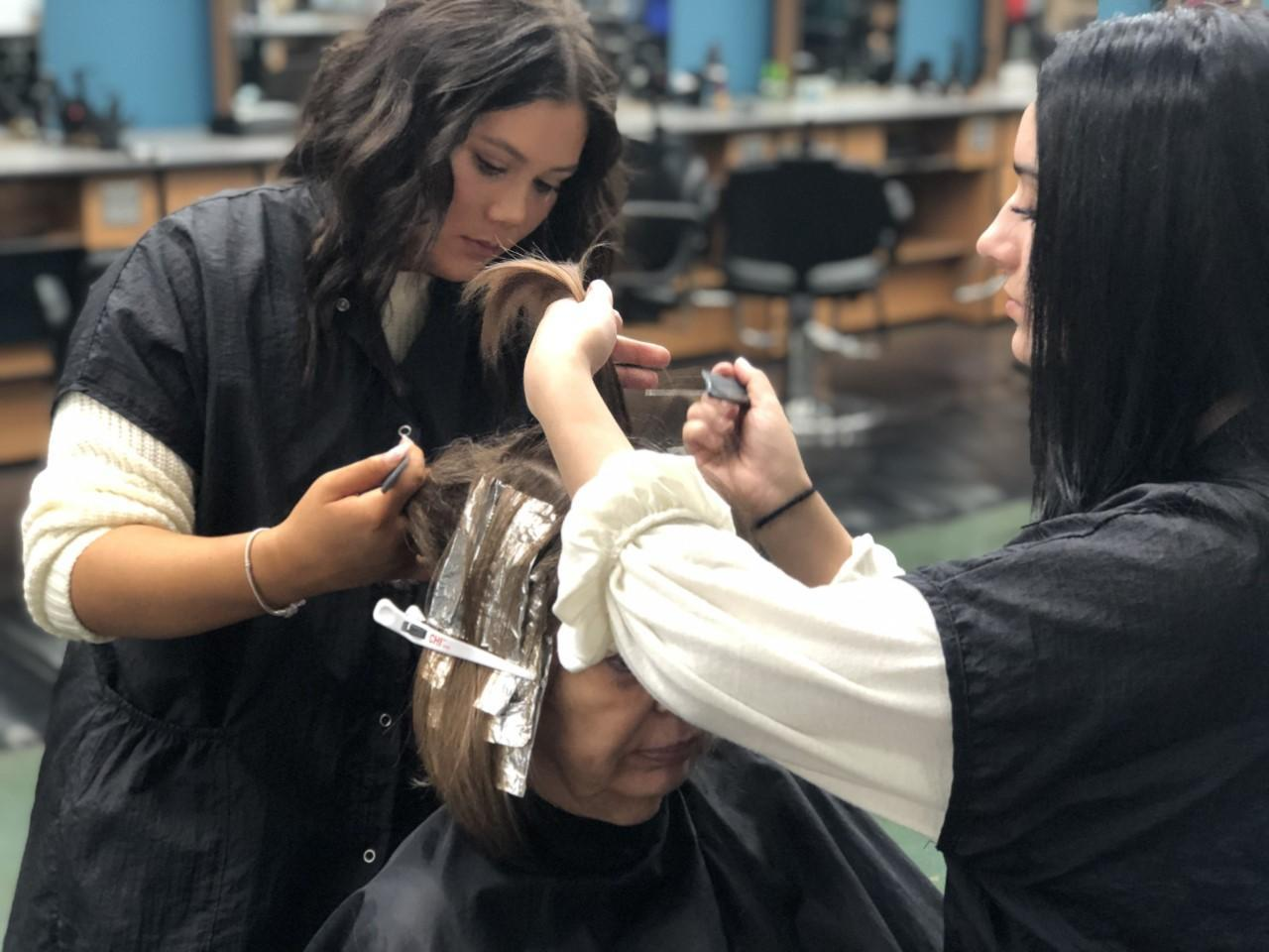 cosmetology students coloring hair
