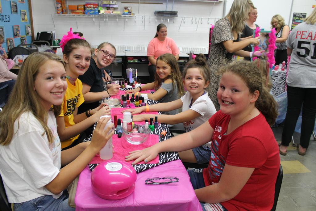 Students get manicure by CHS cheerleaders at Fall Festival Princess Makeover.