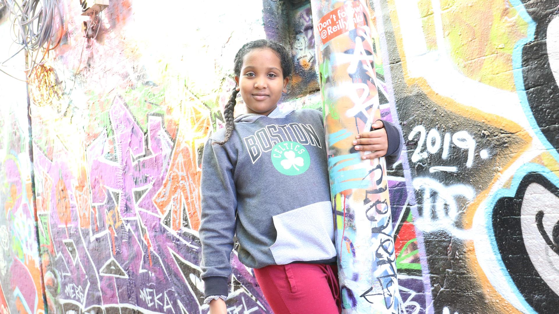 Student posing with graffiti artwork