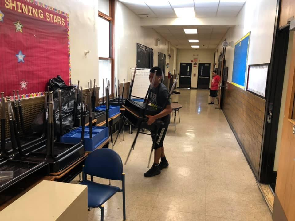 two boys taking the desks and chairs out of a classroom into the hallway