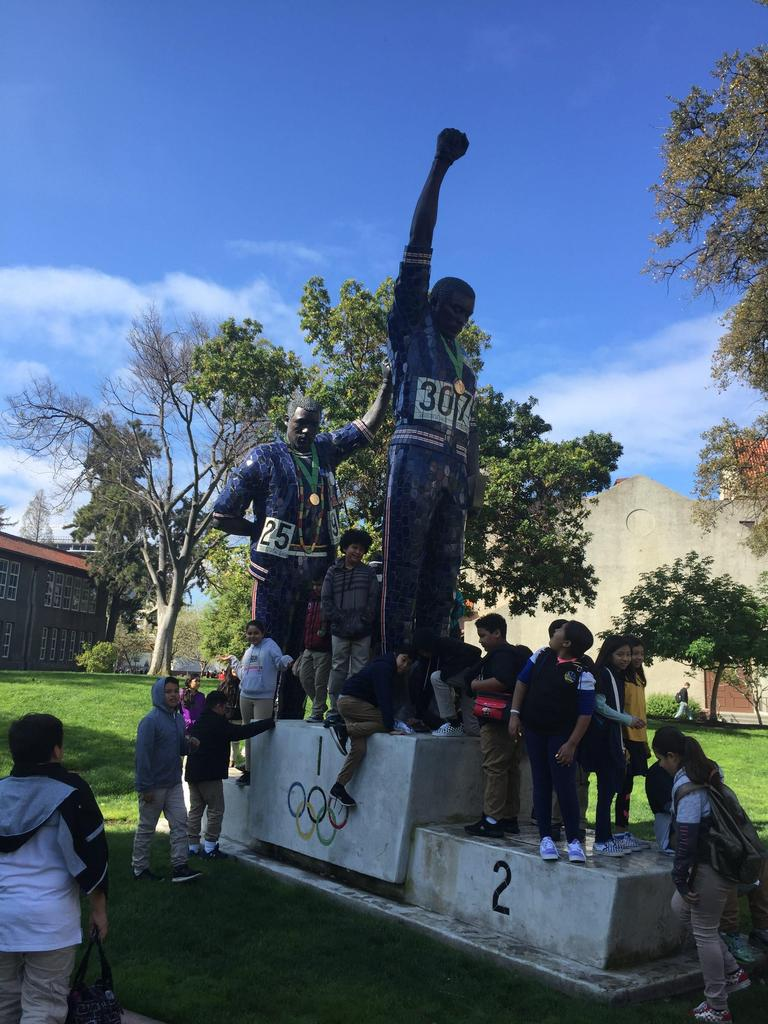 group of fifth grade students surrounding athlete statues
