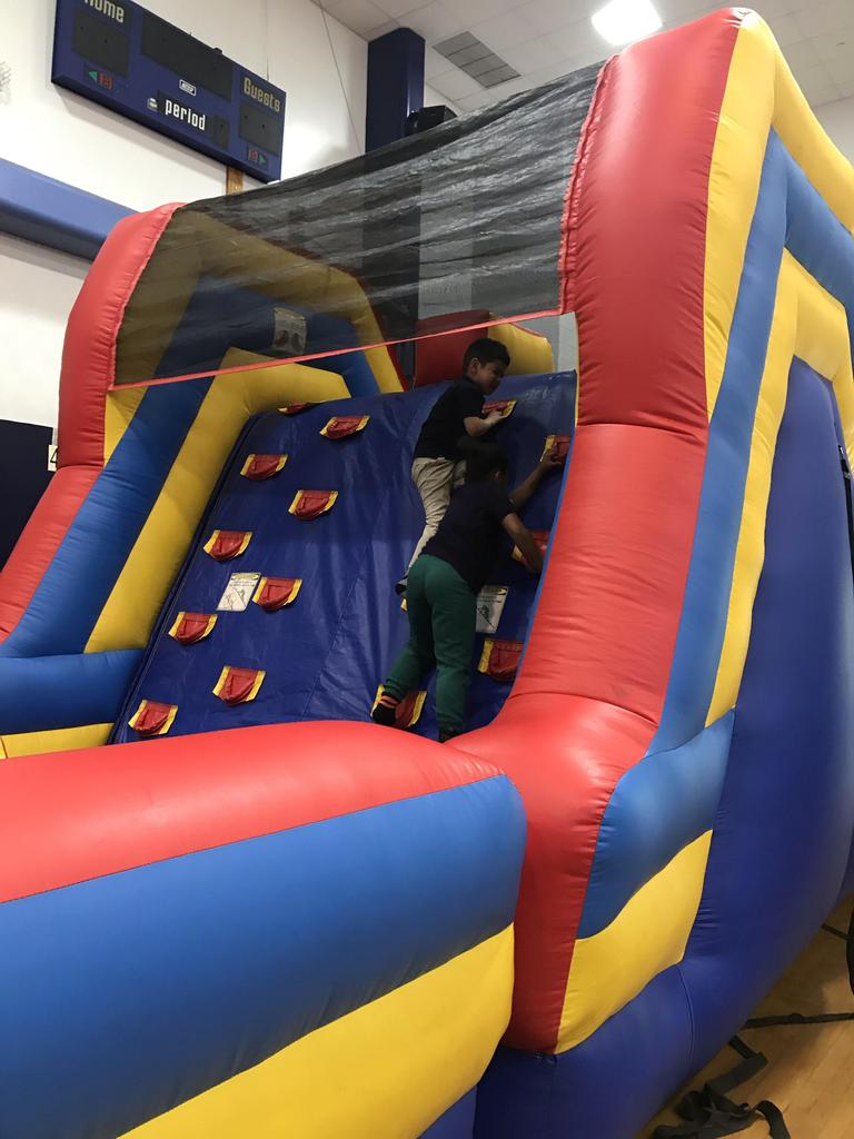 two kids climbing the first part of the the bouncy house
