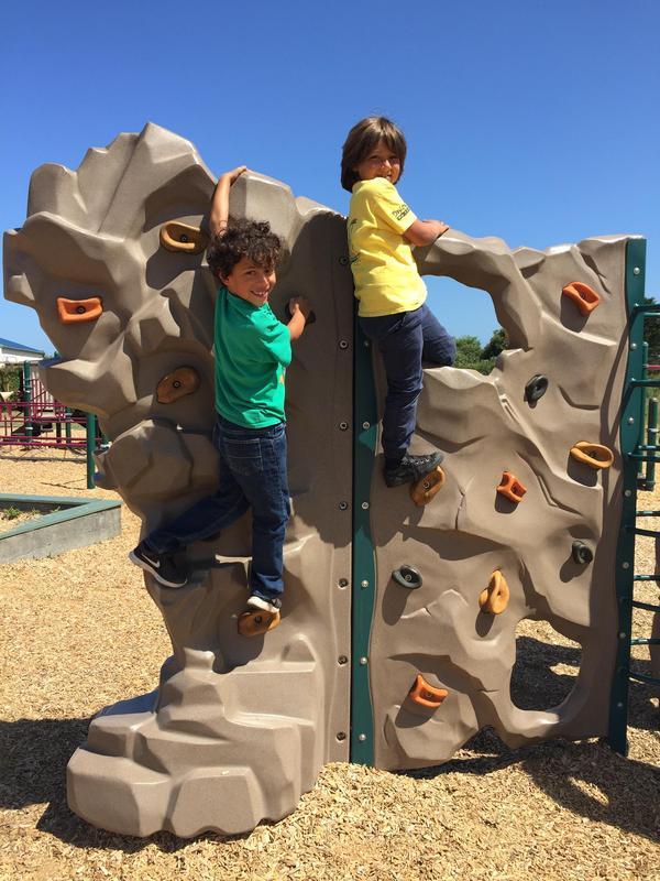 Boys using climbing wall on playground