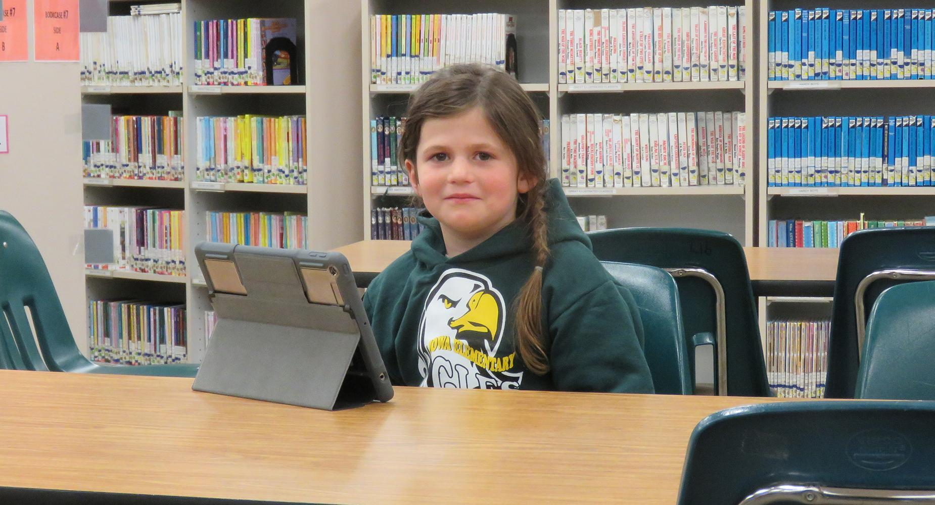 Girl in green Iowa Elementary sweatshirt sits at a table with an iPad in the library.