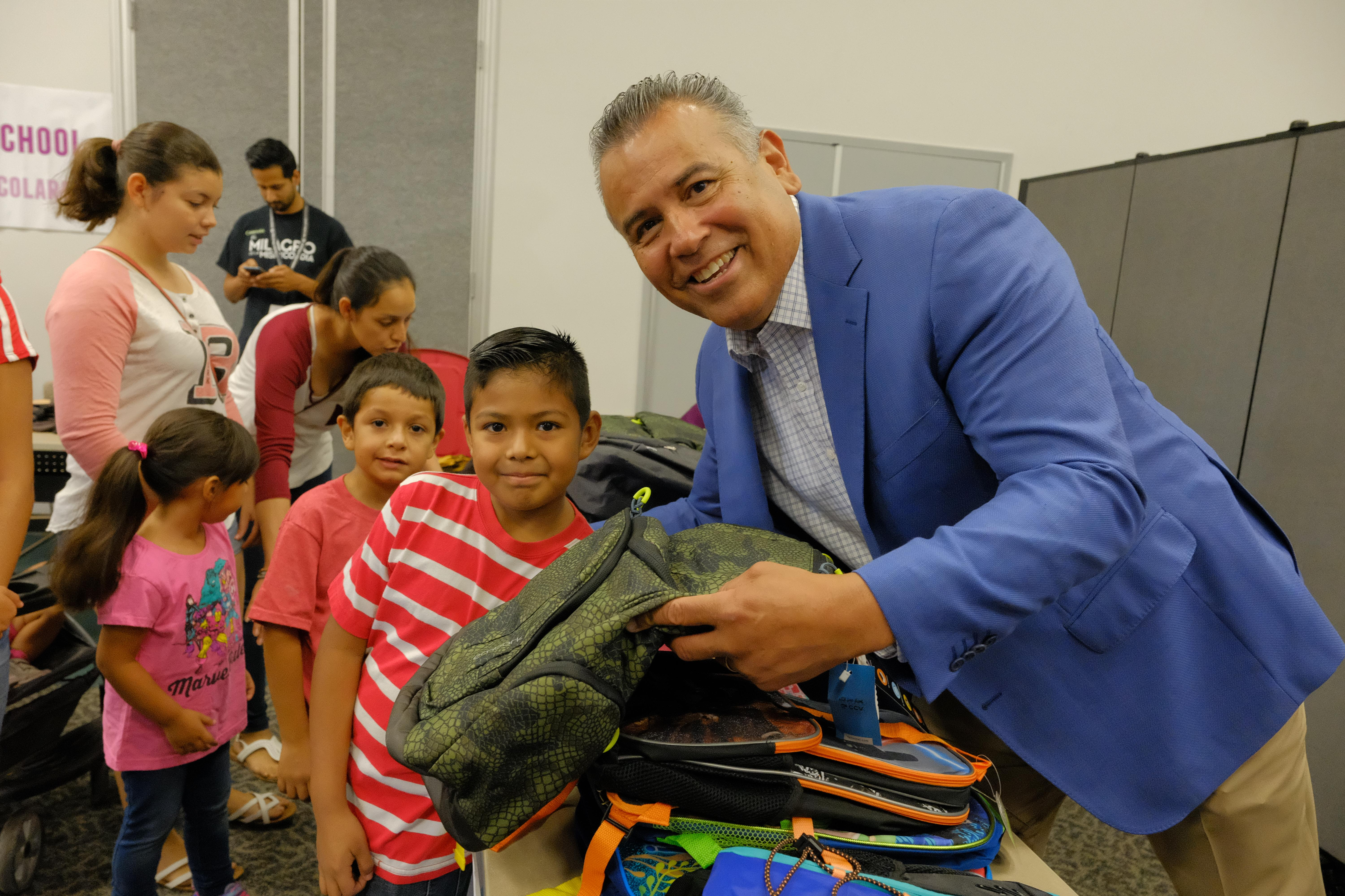 Superintendent Richard Martinez with student at the backpack giveaway.