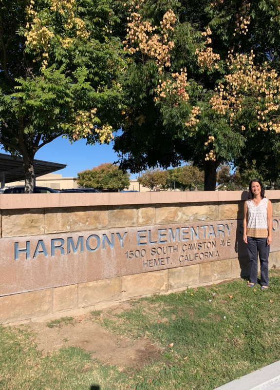 Cristen Yacovelli standing in front of a Harmony sign.