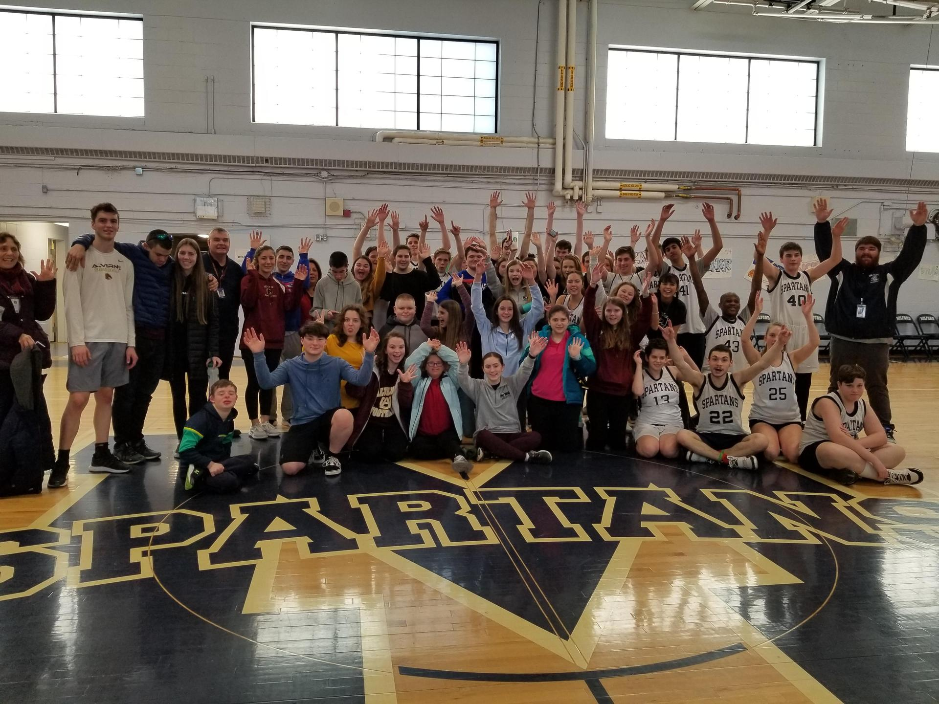 Unified Basketball team with Alvirne's basketball team raising hands in victory