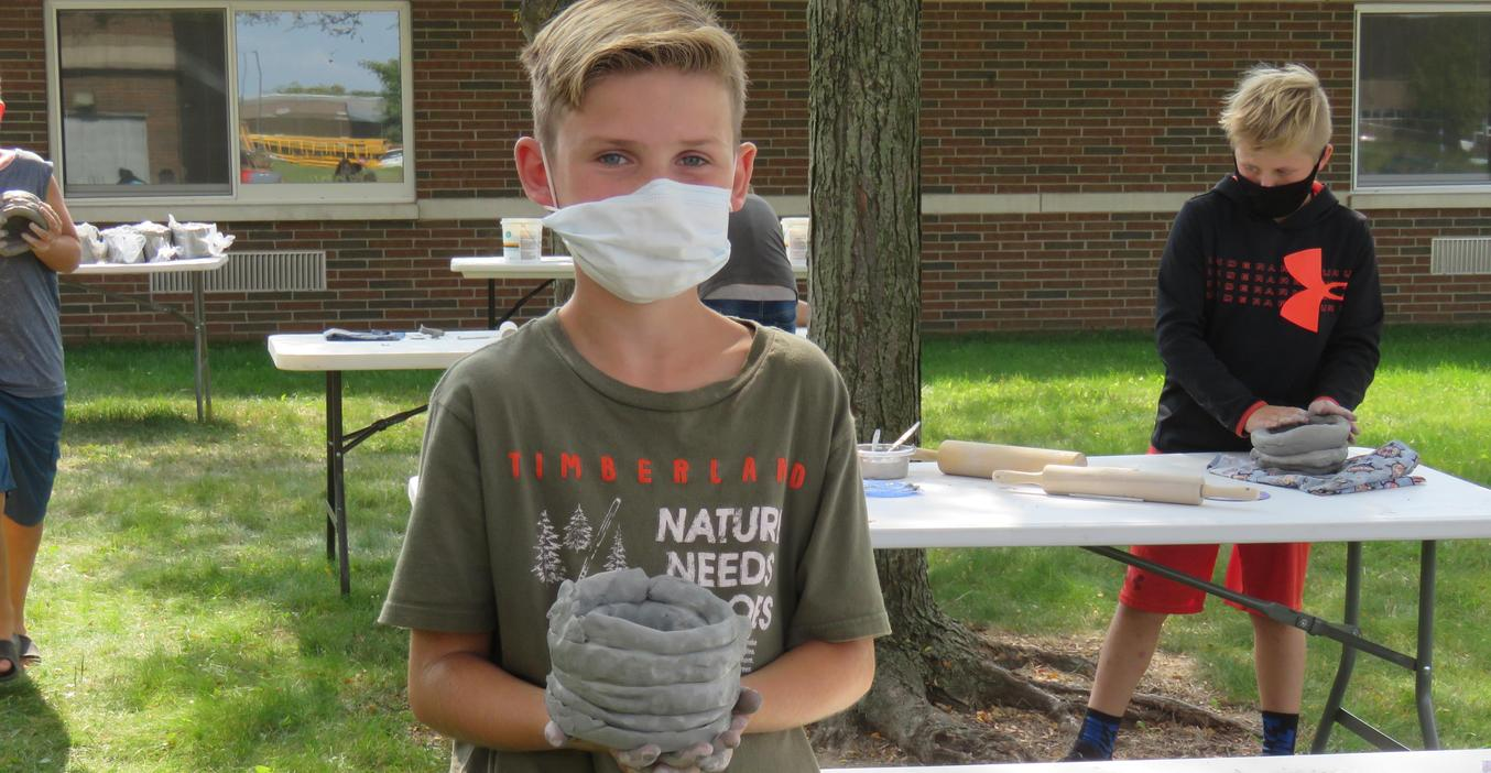 A Page 5th grader proudly shows his completed first step in a pottery project.