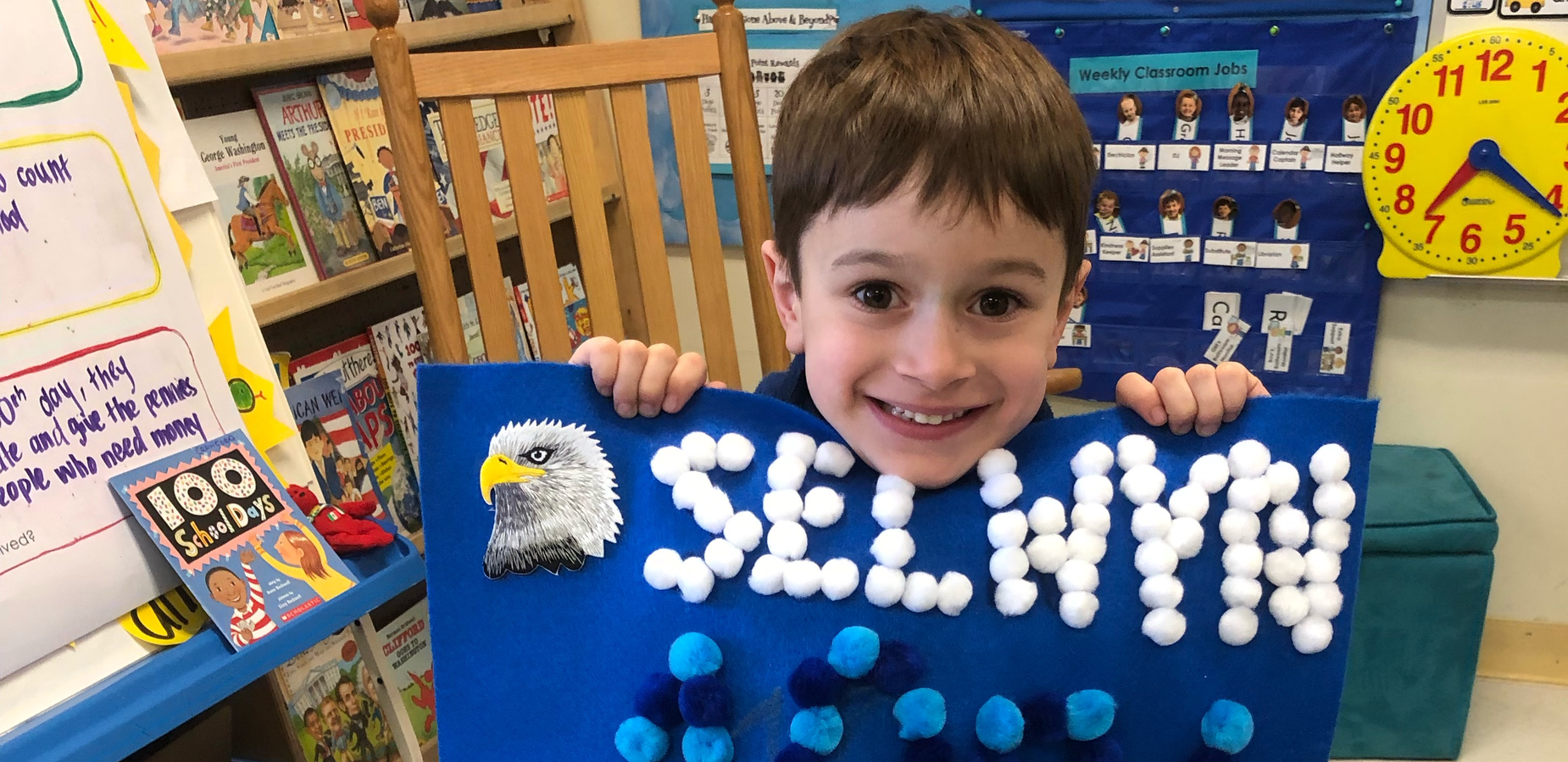 Kindergarten student holding 100th day project
