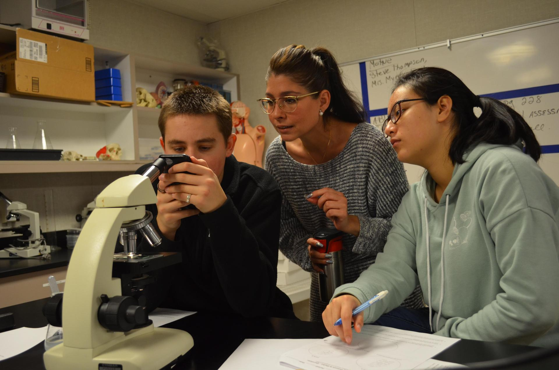 Ms. Acosta working with biology students to photograph plant cells.