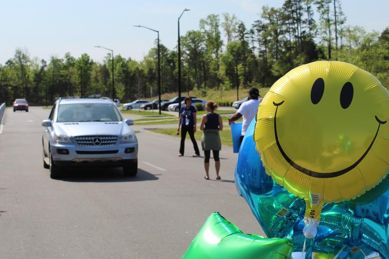 Upper School & Admin Team hand out caps and gowns to our seniors drive-thru style! Featured Photo