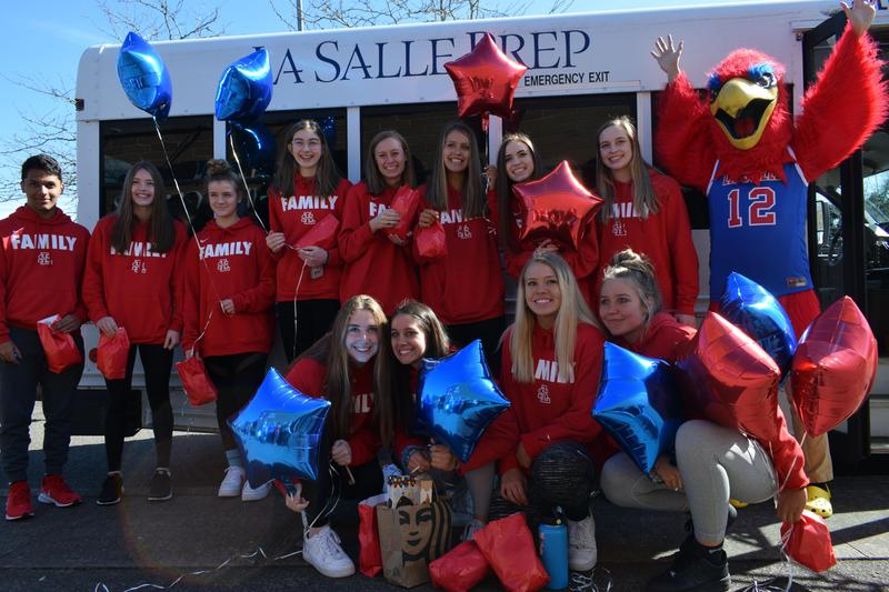 girls basketball tplayers in front of bus