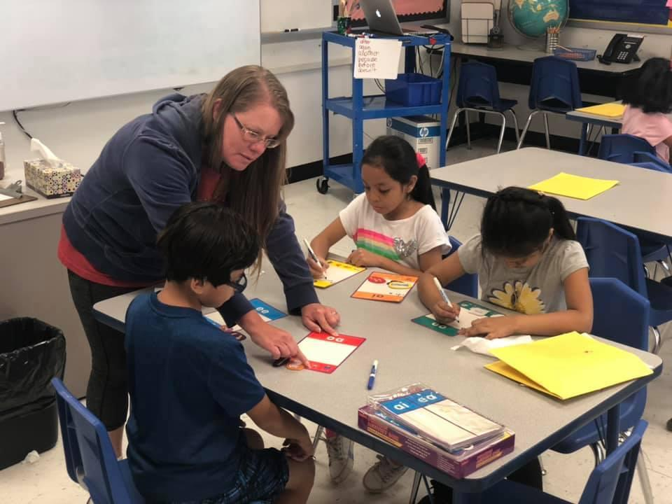teacher working with three children on coding assignment