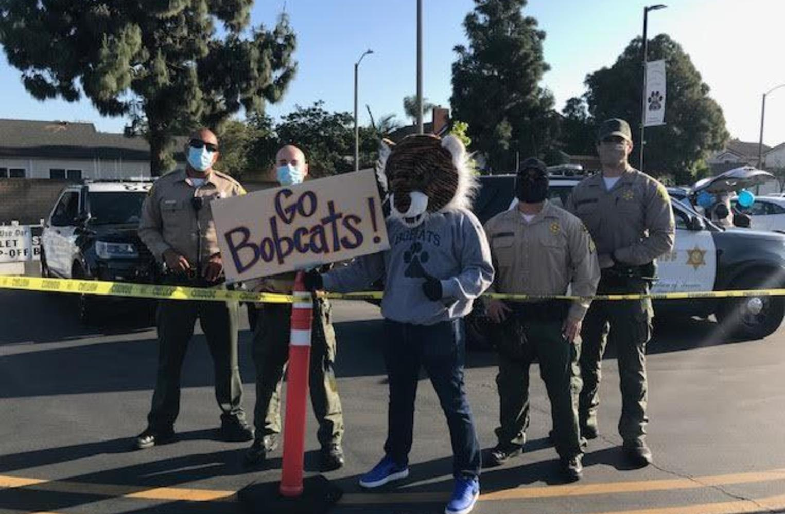 Man in bobcat costume with Sheriffs