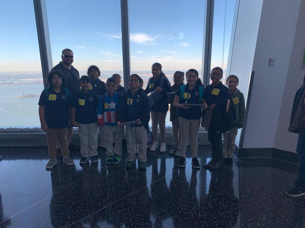 group of kids standing with Mr. Black with the NY skyline as the background
