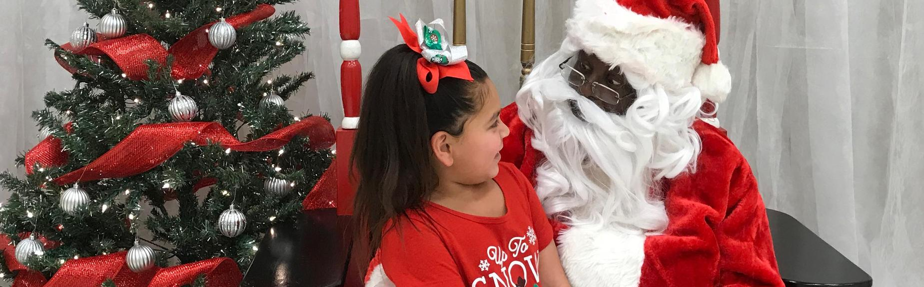 Santa visits with an Elementary student at the Merry Mustang Market!