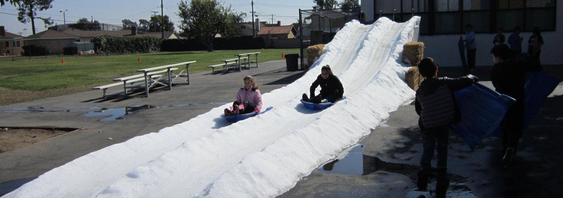 Two girls sled down a hill of snow.