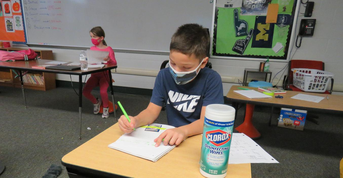 Third-grade students write letters to pen pals in Texas.