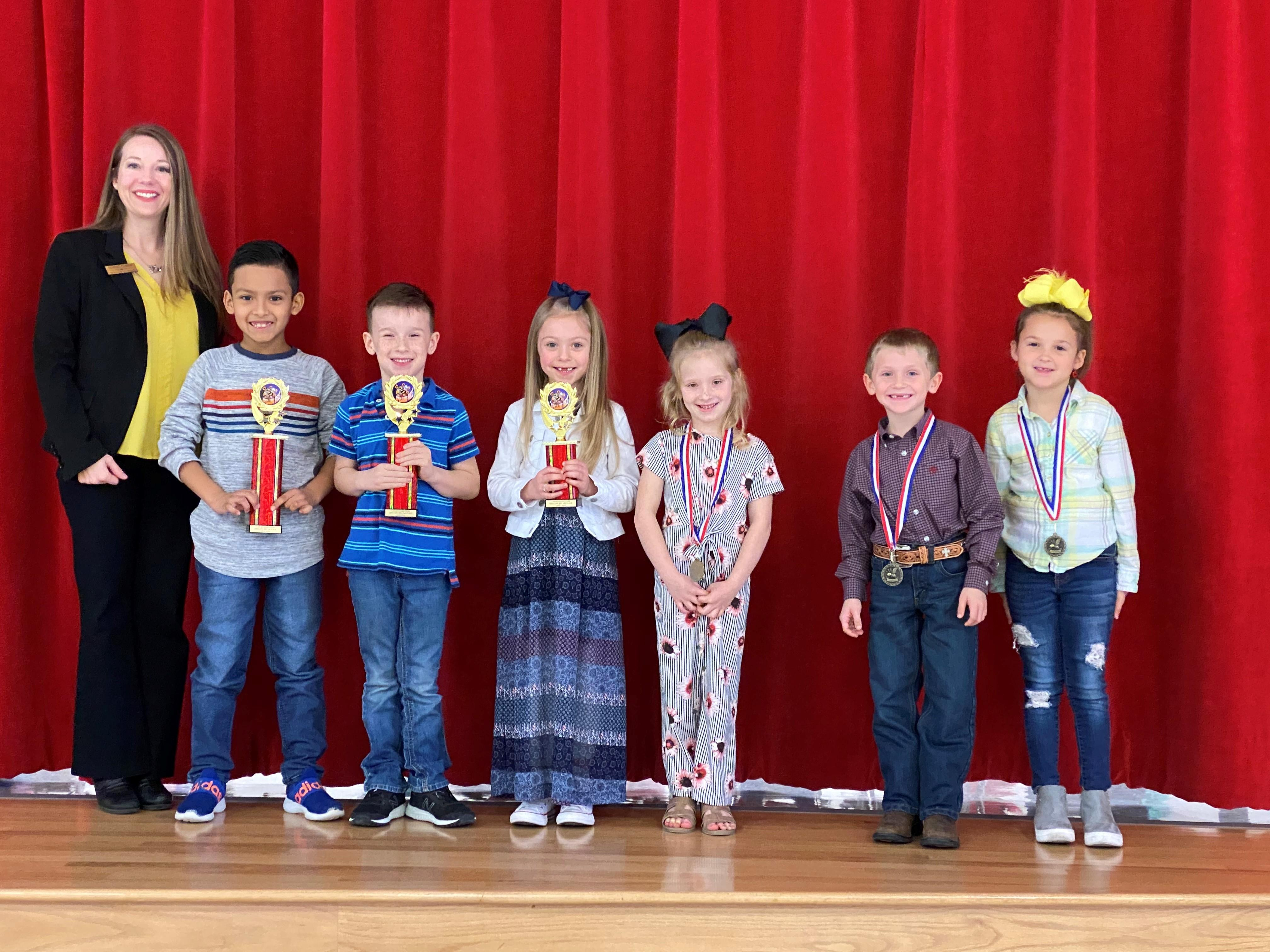 lamar spelling bee winners pictured with principal Mrs. Fowler holding their trophies and medals, 1st through 6th places