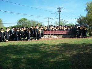 East Davidson Graduates around Pilot sign.