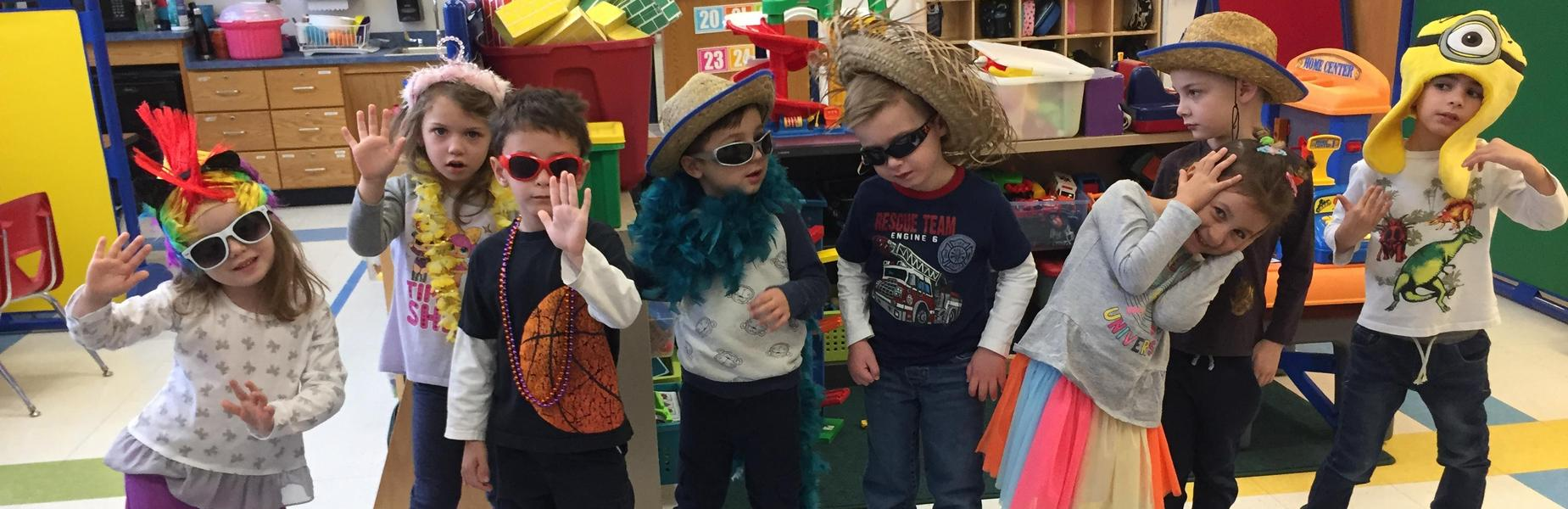 Preschoolers have fun with dress up at Lincoln School.  Pictured here is a line of preschoolers wearing various hats and sunglasses.