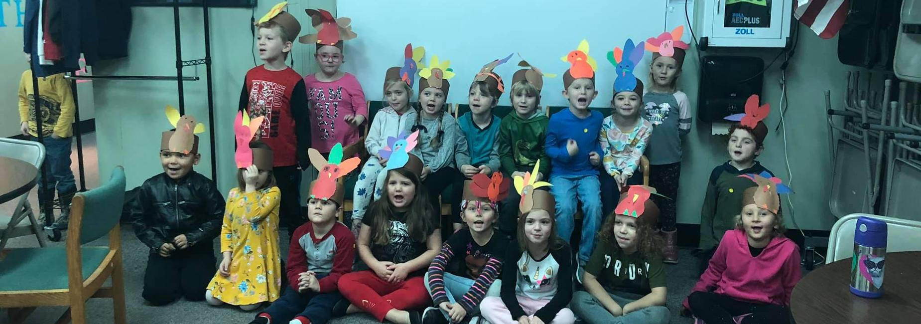 students wearing hats shaped like thanksgiving turkeys